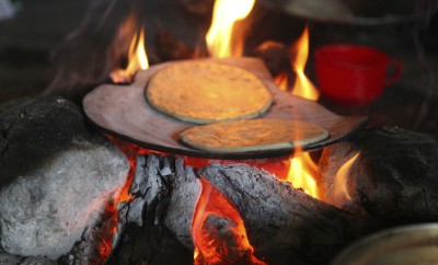 two tortillas cooking on cookfire