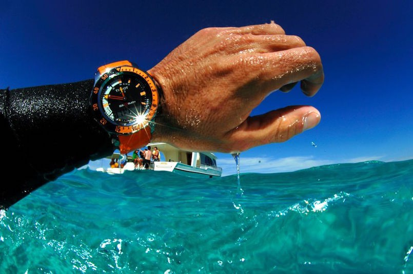 orange and black diving watch on man's wrist in water