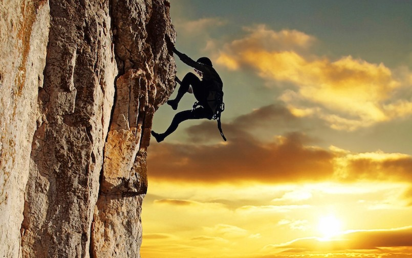 man rock climbing with setting sun in the background