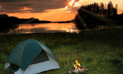 Camping with a campfire and tent by the lake
