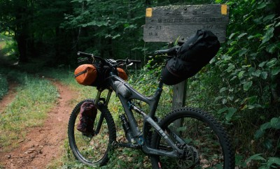 mountain bike resting on sign in the woods