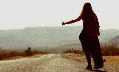 woman hitchhiking on desert road