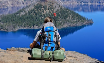 woman sitting on cliff overlooking a lake with a backpack