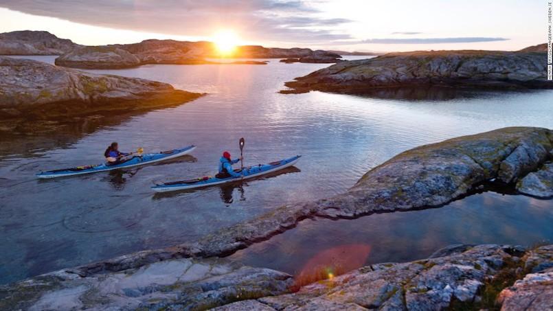 people kayaking around rocks