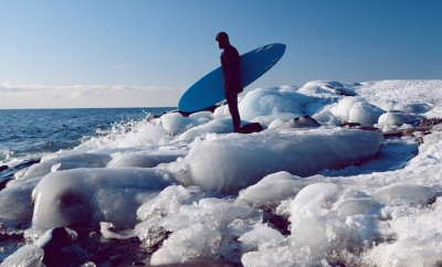 in wetsuit with surfboard on icy shore
