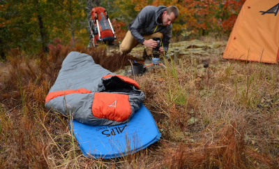 man setting up campsite and sleeping bag on the ground