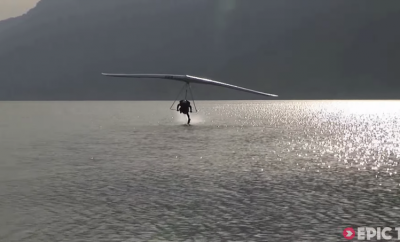 person hang gliding and touching the water