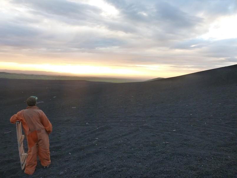 person in orange jumpsuit volcano boarding