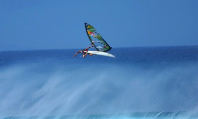 person windsurfing and jumping over a wave