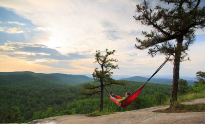 woman sitting in hammock on mountain