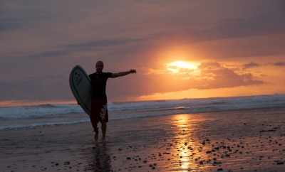 man with surfboard in the setting sun