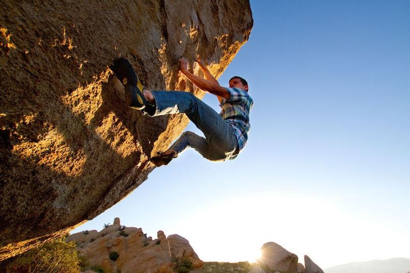 man in plaid shirt bouldering climbing