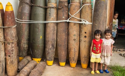 young girls standing by old bombs