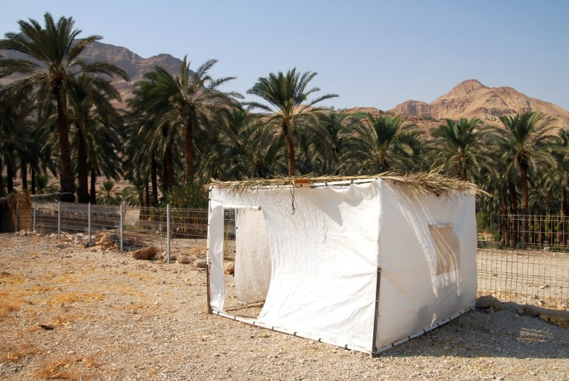 A sukkah in the desert. A sukkah is a temporary hut constructed for use during the week-long Jewish festival of Sukkot. It is topped with branches and often the interior is decorated