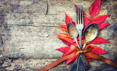 Thanksgiving table setting: cutlery on the autumn background with autumn leaves,ribbon on wooden background:Thanksgiving holidays background concept