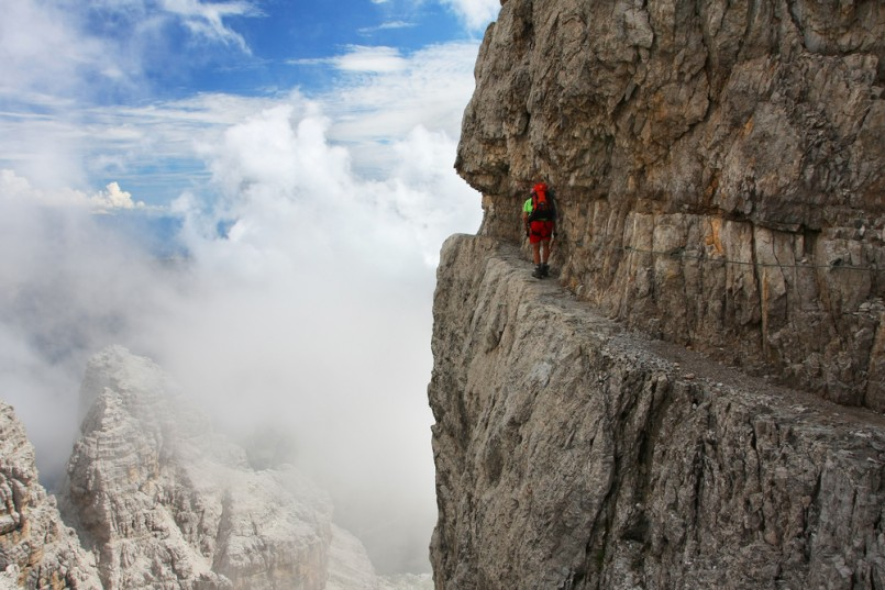 A man going through the difficult part of ferrata - Dolomiti mountains, Dolomiti di Brenta, Italy