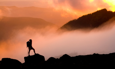 hiker on mountain in clouds at sunset