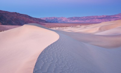 View of a sand dune with mountains in the background from Death Valley National Park. Taken during the early morning light right before sunrise