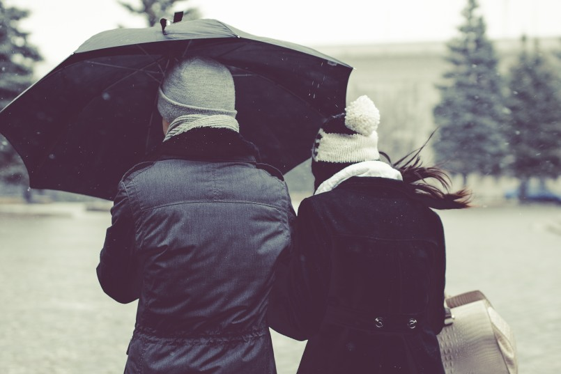 couple walking in snow with coats and umbrella