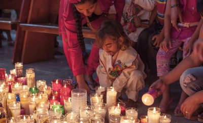young boy dressed as Juan Diego is helped by his mother as he places a candle on a church floor after a mass celebrating the Feast of Our Lady of Guadalupe