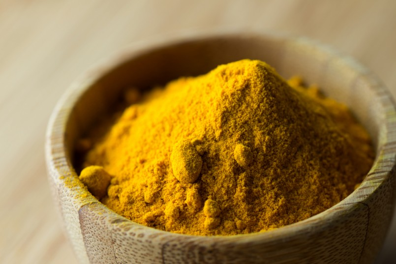 Close up of turmeric powder in wooden bowl
