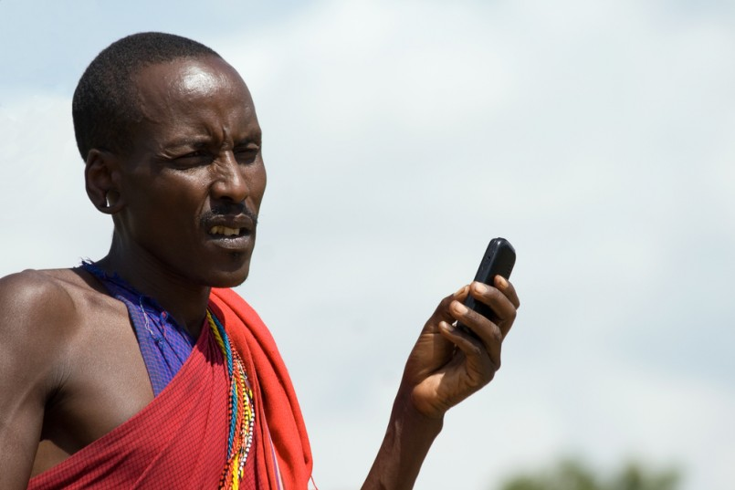 Native Masai with Cellphone in Masai Mara National Park, Kenya