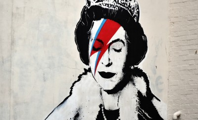 View of a Banksy piece depicting the Queen as David Bowie in his Ziggy Stardust persona seen on a city centre street