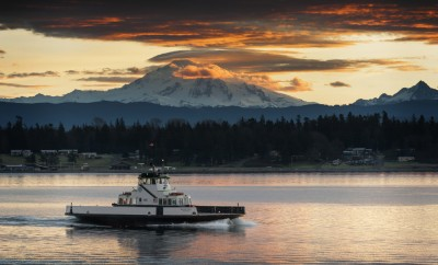 """Ferry and Mt. Baker. The ferryboat """"Whatcom Chief"""" sails from Gooseberry Point to Lummi Island across Hales Pass in the San Juan Islands of Puget Sound. Mt. Baker is seen in the background at sunrise."""