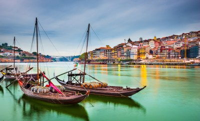 Porto, Portugal old town cityscape on the Douro River with traditional Rabelo boats