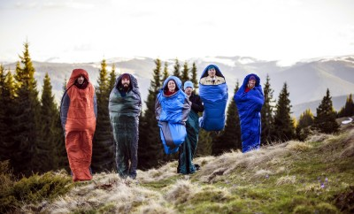 cheering group of hikers jumping in sleeping bags outdoors in mountains during the sunset