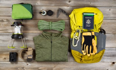 High angled view of organized hiking gear for climbing placed on rustic wooden boards