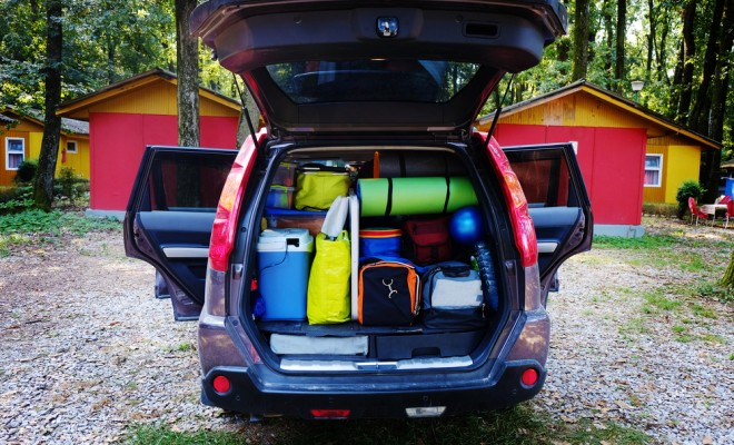 Travel and camping luggage packed in the car trunk. Outdoor wanderlust items. Outdoor, adventures and travel suv