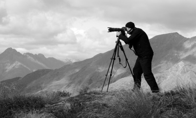 Professional travel on location and nature videographer:photographer (man) photographing and video nature and landscape outdoor.(BW)