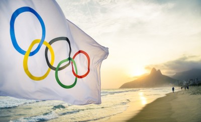 RIO DE JANEIRO, BRAZIL - OCTOBER 27, 2015: An Olympic flag flutters in the wind in front of the sunset skyline at Ipanema Beach.