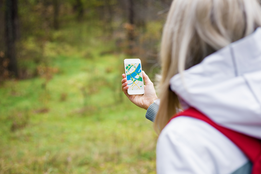 Woman geocaching in forest and using map app on smartphone