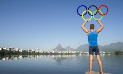 Athlete holding Olympic rings stands on the shore of Lagoa Rodrigo de Freitas lagoon, a venue for the Summer Games