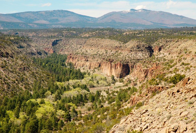 native american indian cliff dwellings in a canyon, with mountains in the distance