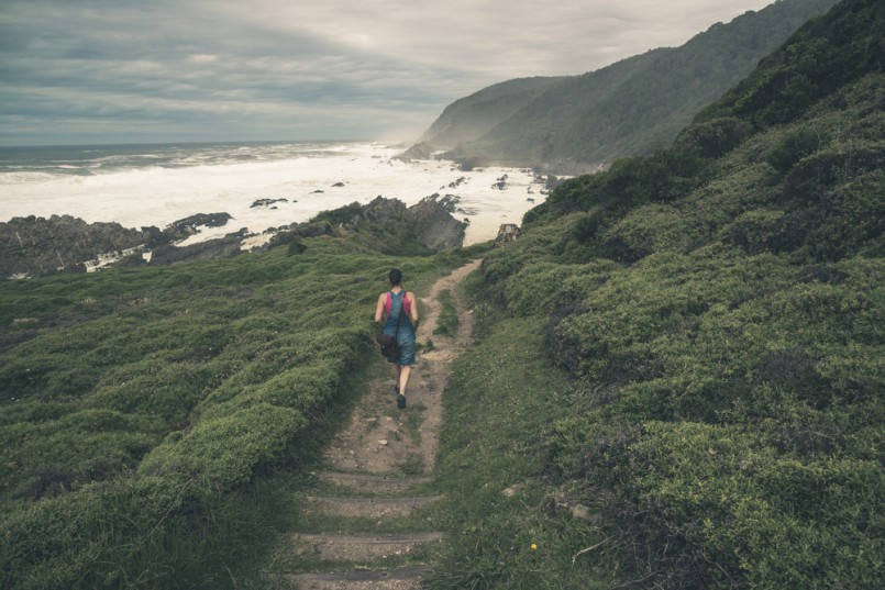 Female tourist walking on trail along the wild coast of Tsitsikamma National Park. Eastern Cape. South Africa
