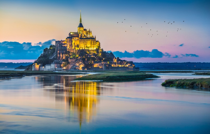Panoramic view of famous Le Mont Saint-Michel tidal island in beautiful twilight during blue hour at dusk, Normandy, northern France