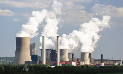 A coal-fired power station in the distance in agricultural landscape. The power station Niederaussem has the second highest cooling tower in the world with a height of 200m.