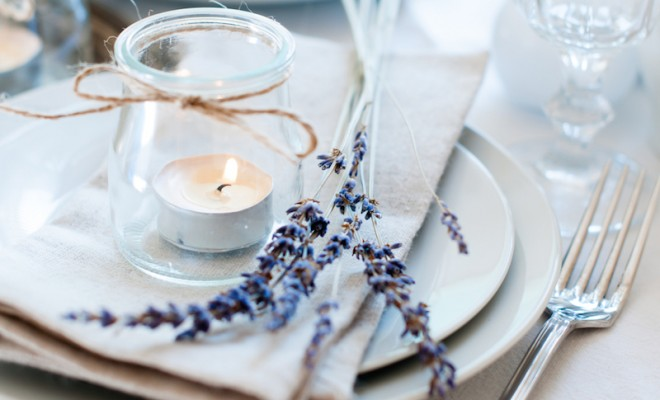 dining table setting at provence style with candles lavender vintage crockery and cutlery closeup