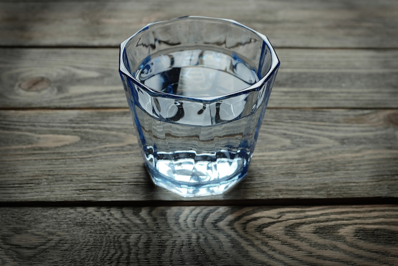 glass of water on the table wooden background
