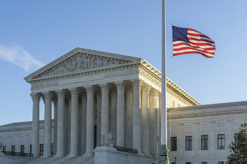 WASHINGTON, DC, USA - FEBRUARY 14, 2016: Flags fly at half-staff at the United States Supreme Court as the sun rises on the first day after Justice Antonin Scalia's death was announced.