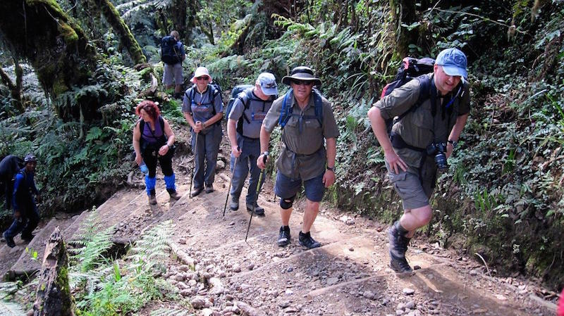 group of tired hikers climbing mt kilimanjaro in africa