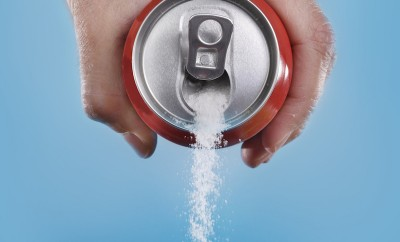 hand holding soda can pouring a crazy amount of sugar in metaphor of sugar content of a refresh drink isolated on blue background in healthy nutrition diet and sweet addiction concept