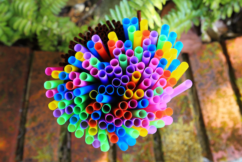 colored drinking straws with nature background - close up