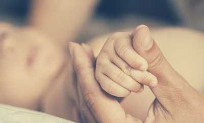 Mother with her newborn baby care hands