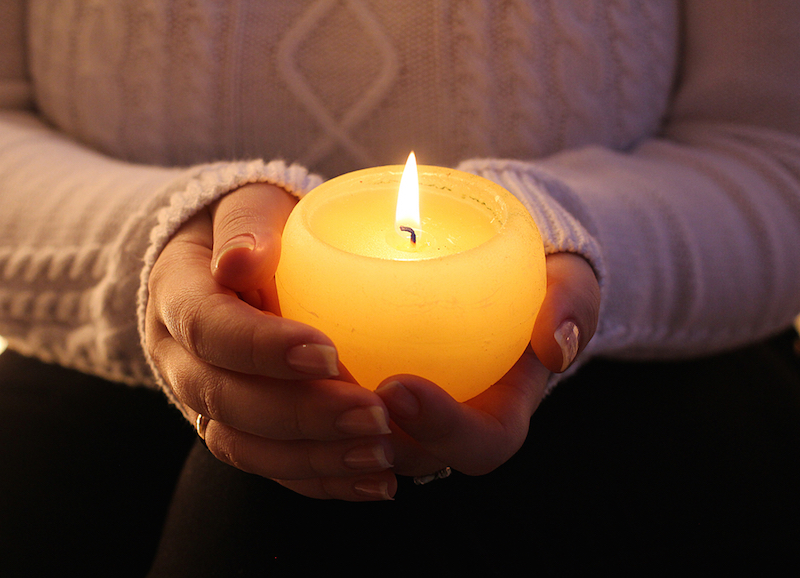 burning candle in the hands of a girl christmas candles
