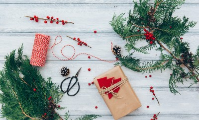 Christmas background with hand crafted gifts, presents on rustic wooden table. Christmas or New year DIY packing. Holiday decor concept. Overhead, flat lay, top view