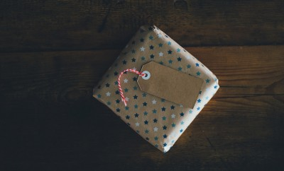 brown wrapping paper holiday gift present with stars on wood floor dark